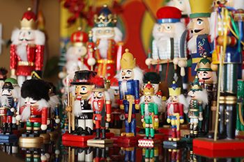 a large collection of various, colorful toy Christmas soldiers and Nutcrackers stand together